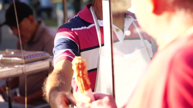 mature man selling churros at street - bancarella video stock e b–roll