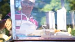 Mature Man selling churros at street
