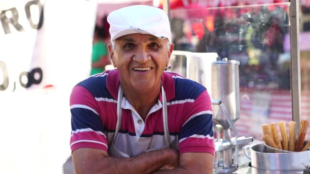 mature man selling churros at street - market trader stock videos & royalty-free footage