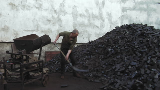 WS Mature man shoveling coal, Berlin, Germany