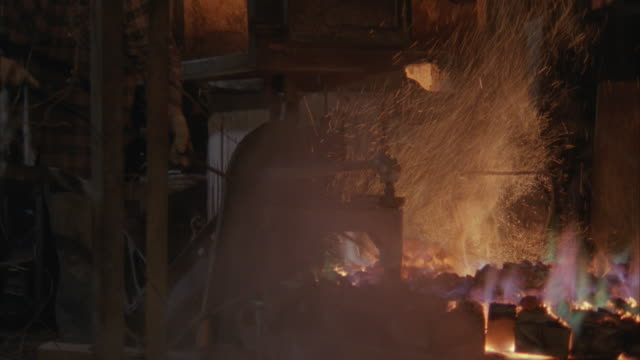 ms, pan, mature man shoveling hot coals into furnace in cable and wire factory - プレイドシャツ点の映像素材/bロール