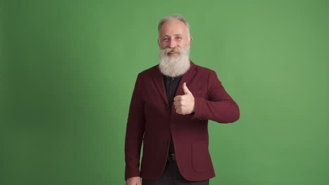 mature man  shows copy space and shows thumbs up on green background . one person - coloured background stock videos & royalty-free footage