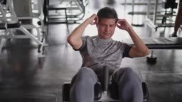 Mature man sit up and exercise in fitness gym.