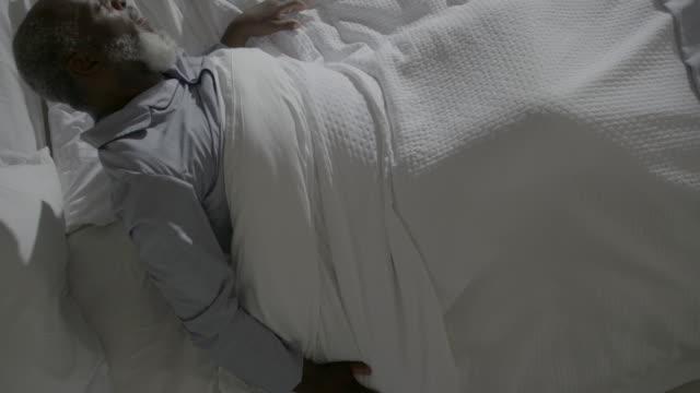 vídeos de stock e filmes b-roll de a mature man sits up in bed. - bocejar