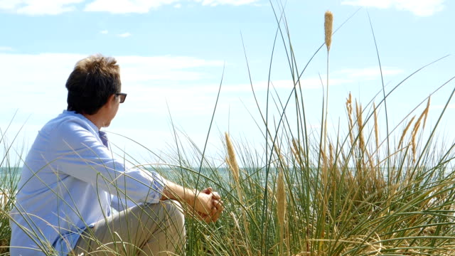 Mature man sitting by sand dunes at the beach. Dolly shot.