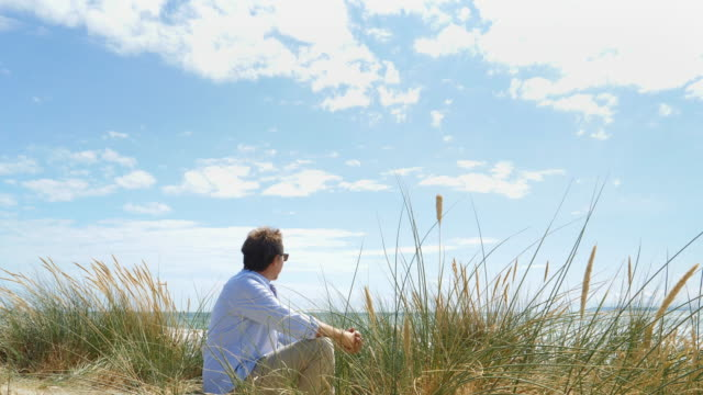 Mature man sitting by sand dunes at the beach.