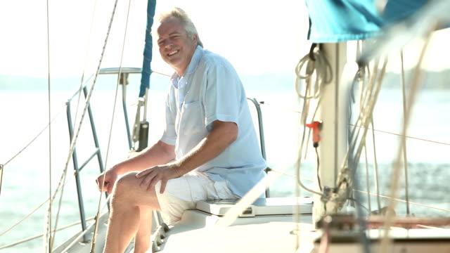 vídeos de stock e filmes b-roll de mature man sitting on deck of luxury sailboat - abundância