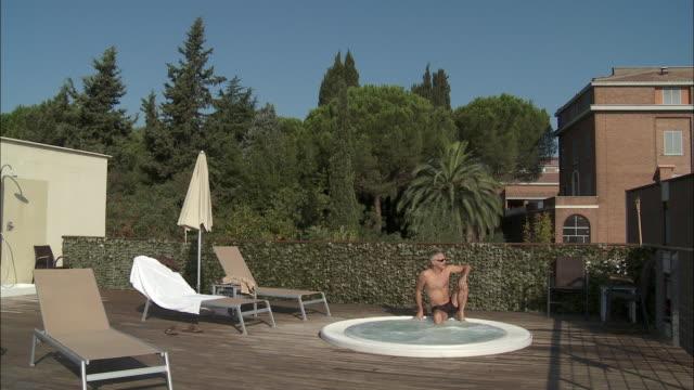 vídeos de stock e filmes b-roll de ws mature man sitting on edge of outdoor hot tub, rome, italy - olhar de lado