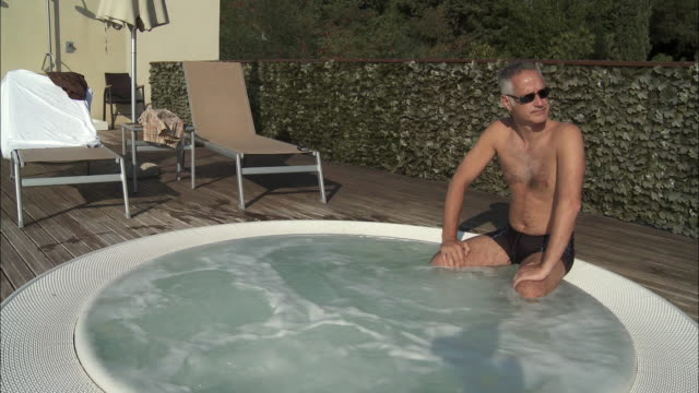 MS HA Mature man sitting on edge of outdoor Jacuzzi, Rome, Italy