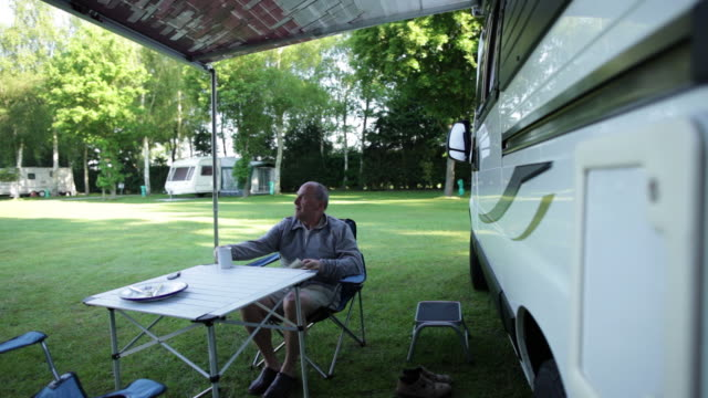 ws mature man sitting reading and drinking tea in front of  camper van/bungay/suffolk/uk - 中年の男性一人点の映像素材/bロール