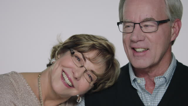 CU SLO MO. Mature man smiles lovingly at wife as she leans her head on his shoulder.