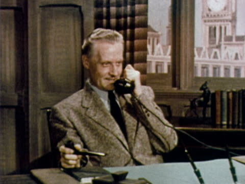 1960 MS mature man smoking pipe and talking on telephone at office desk / USA