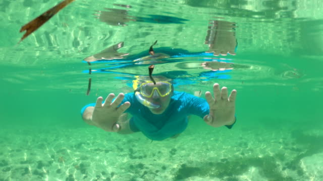 mature man snorkeling and showing thumbs up - indian ocean stock videos & royalty-free footage