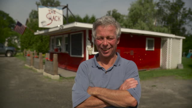 ms mature man standing in front of americana type roadside snack bar / stowe, vermont, usa - 道ばた点の映像素材/bロール