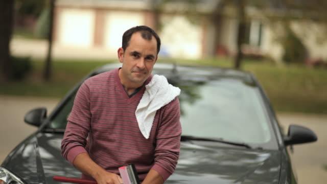 vídeos de stock e filmes b-roll de ms mature man standing in front of his car holding squeegee / neenah, wisconsin, usa  - em frente de