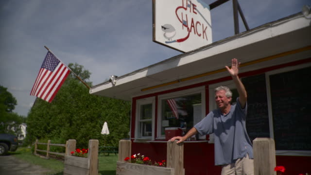 ms pan mature man standing in front of snack bar and waving hand / stowe, vermont, usa   - 道ばた点の映像素材/bロール