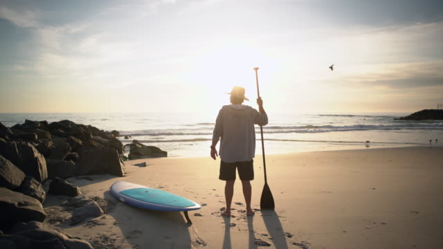 stockvideo's en b-roll-footage met ws rv mature man standing on the beach with his paddleboard - rear view