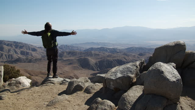 rv mature man standing on the edge of a cliff with arms outstretched - boulder stock videos & royalty-free footage