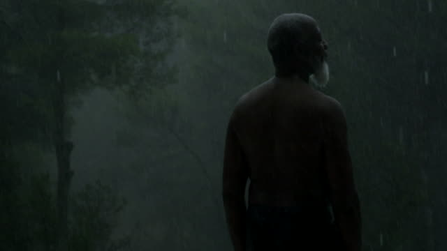 mature man stands out in the rain (panning) - tropical tree stock videos & royalty-free footage