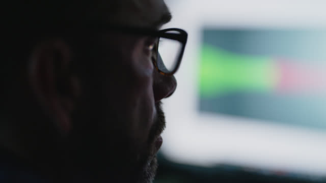 cu mature man stares at computer monitor in dark room, puts on eyeglasses - computer graphic stock-videos und b-roll-filmmaterial