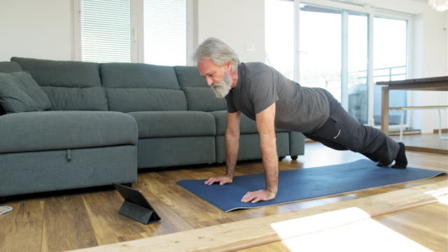 mature man stretching at home on exercise mat - home workout stock videos & royalty-free footage