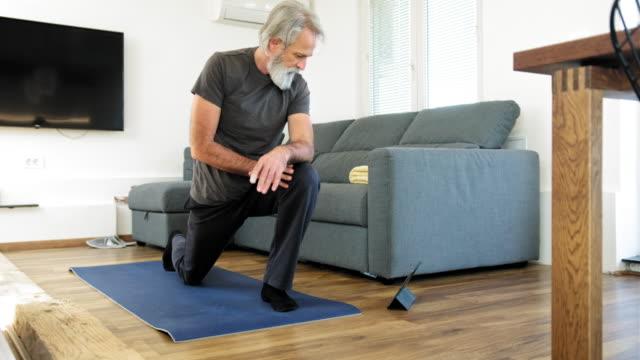 vídeos de stock e filmes b-roll de mature man stretching at home on exercise mat - homens adultos