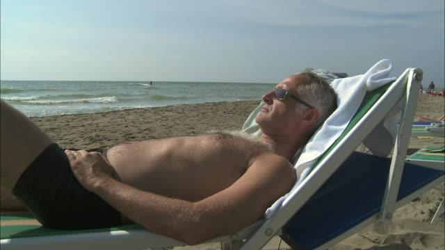 MS Mature man sunbathing on lounge chair on beach, Rome, Italy