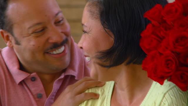 CU, TU, TD, Mature man surprising woman with red roses, Richmond, Virginia, USA
