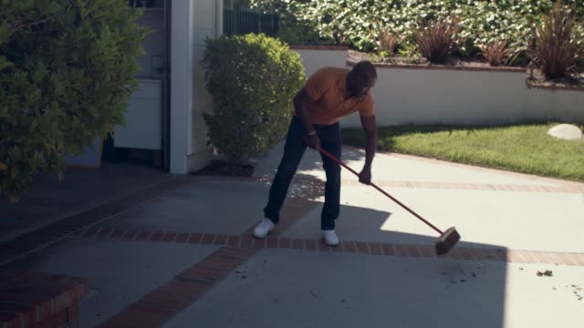 mature man sweeping driveway of his house - modern manhood stock videos & royalty-free footage