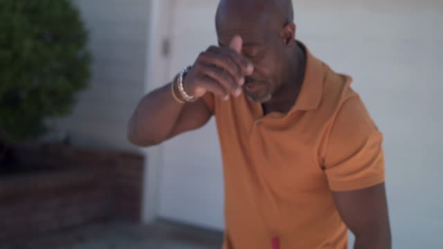 vidéos et rushes de mature man sweeping driveway, sweating, stretching - sueur