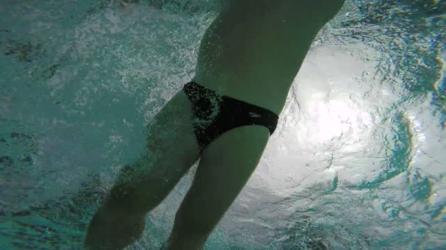 vídeos de stock, filmes e b-roll de mature man swimming front crawl, shot from underwater looking up. - calções de corrida