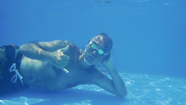 mature man swimming underwater in pool - vergnügen stock-videos und b-roll-filmmaterial