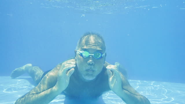 mature man swimming underwater in pool - skill stock videos & royalty-free footage