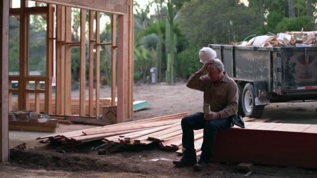 WS Mature man taking a break on a building site