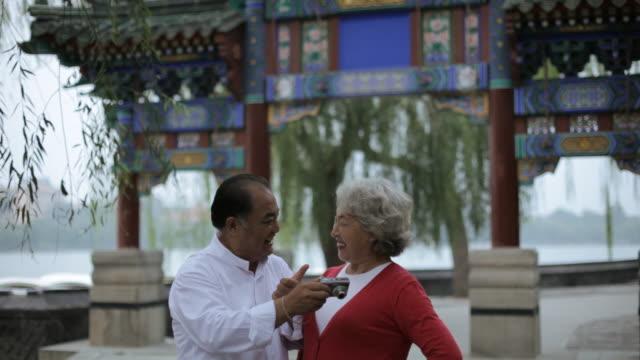 MS Mature man taking photo of elderly woman in front of traditional Chinese gate / Beijing, China