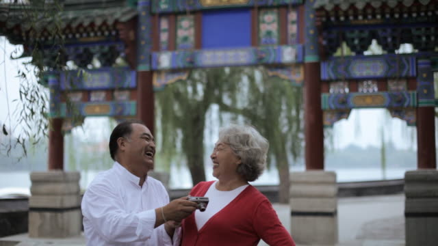 ms mature man taking photo of elderly woman in front of traditional chinese gate / beijing, china - see other clips from this shoot 195 stock videos and b-roll footage