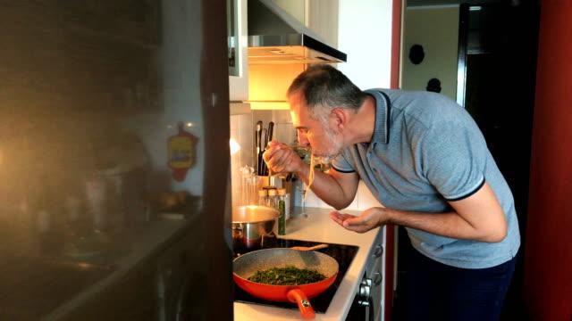 Mogen Man provsmakning mat att han förberett