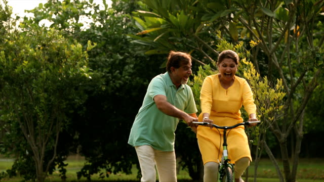vídeos y material grabado en eventos de stock de ms zi mature man teaching his wife to ride bicycle in backyard / delhi, india - pareja madura