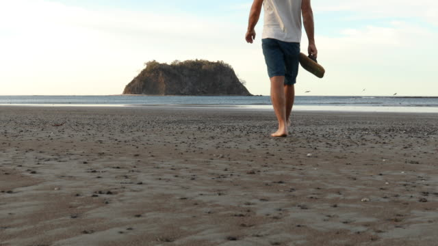 mature man traverses deserted beach at sunrise - shorts stock videos & royalty-free footage
