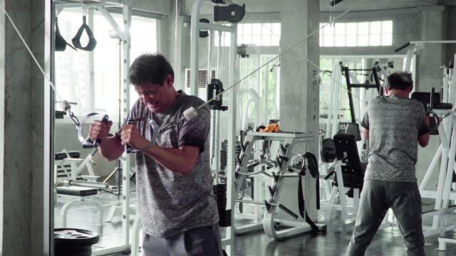 stockvideo's en b-roll-footage met volwassen man probeert hard te trekken stretching kabel - tanden op elkaar klemmen