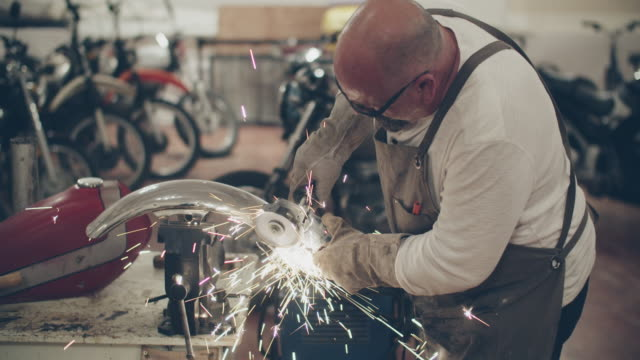 mature man using a grinder in a motorcycle repair shop - completely bald stock videos & royalty-free footage