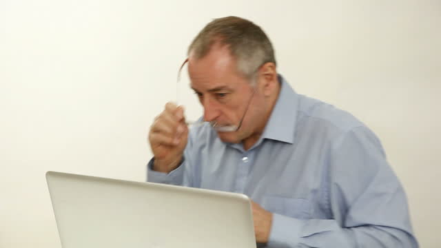 Mature man using a laptop at his desk, then leaving.