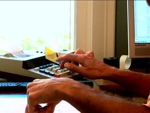 mature man using calculator - addierrolle stock-videos und b-roll-filmmaterial