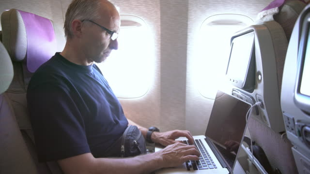 ms mature man using laptop on the airplane - passenger cabin stock videos & royalty-free footage