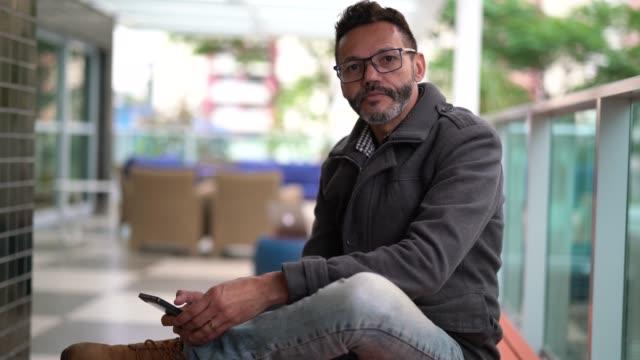 vidéos et rushes de mature man en utilisant mobile au home office - portrait - 50 54 ans