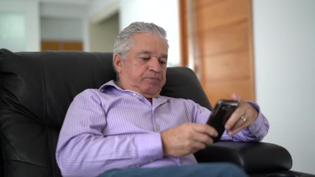 vidéos et rushes de mature man avec mobile à la maison - un seul homme