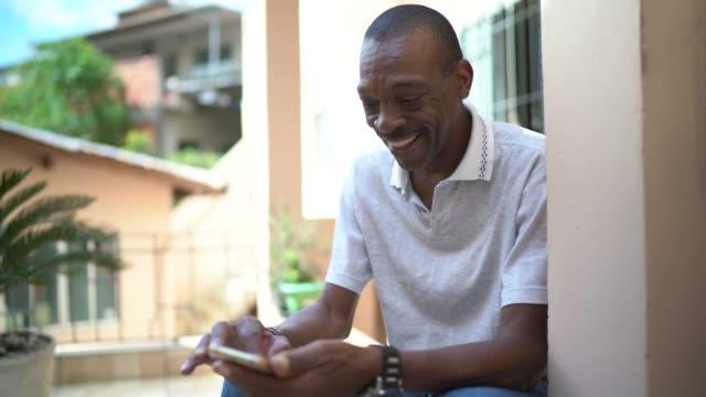 vídeos y material grabado en eventos de stock de hombre maduro usando el teléfono móvil en casa - afro