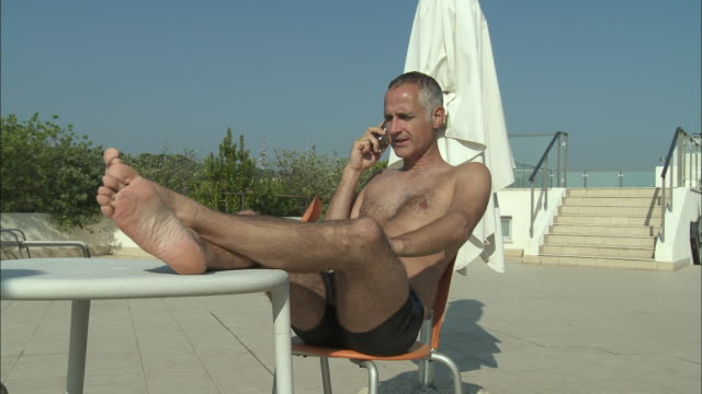 ms mature man using mobile phone, sitting by swimming pool, rome, italy - legs crossed at ankle stock videos and b-roll footage