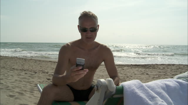 vídeos y material grabado en eventos de stock de ms mature man using mobile phone, sitting on lounge chair on beach, rome, italy - bañador de hombre