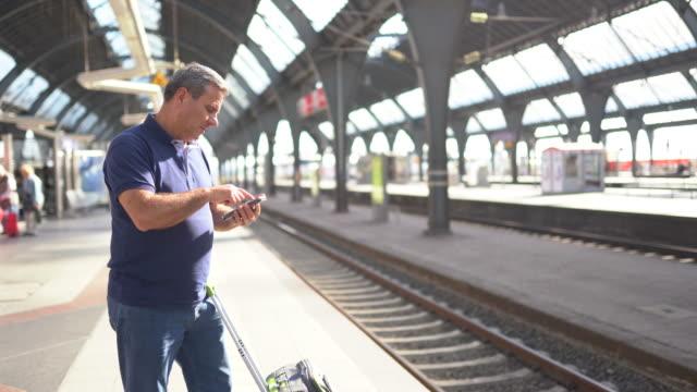 vidéos et rushes de homme mûr utilisant le téléphone à la gare centrale de cologne - quai de gare